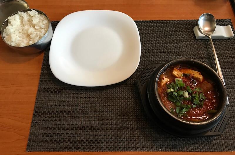 cele mai bune locuri cu mancare din Bucuresti restaurant seoul Supa picantă din Kimci și carne de porc cu un bol de orez simpluKimci Cigae
